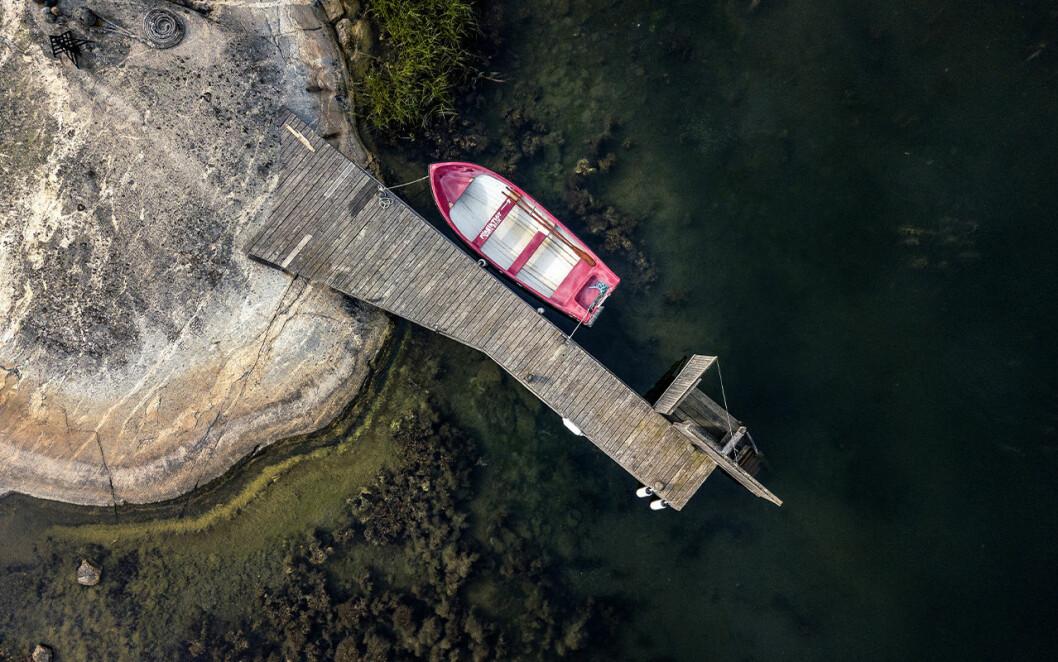 Roddbåt förtöjd vid brygga.