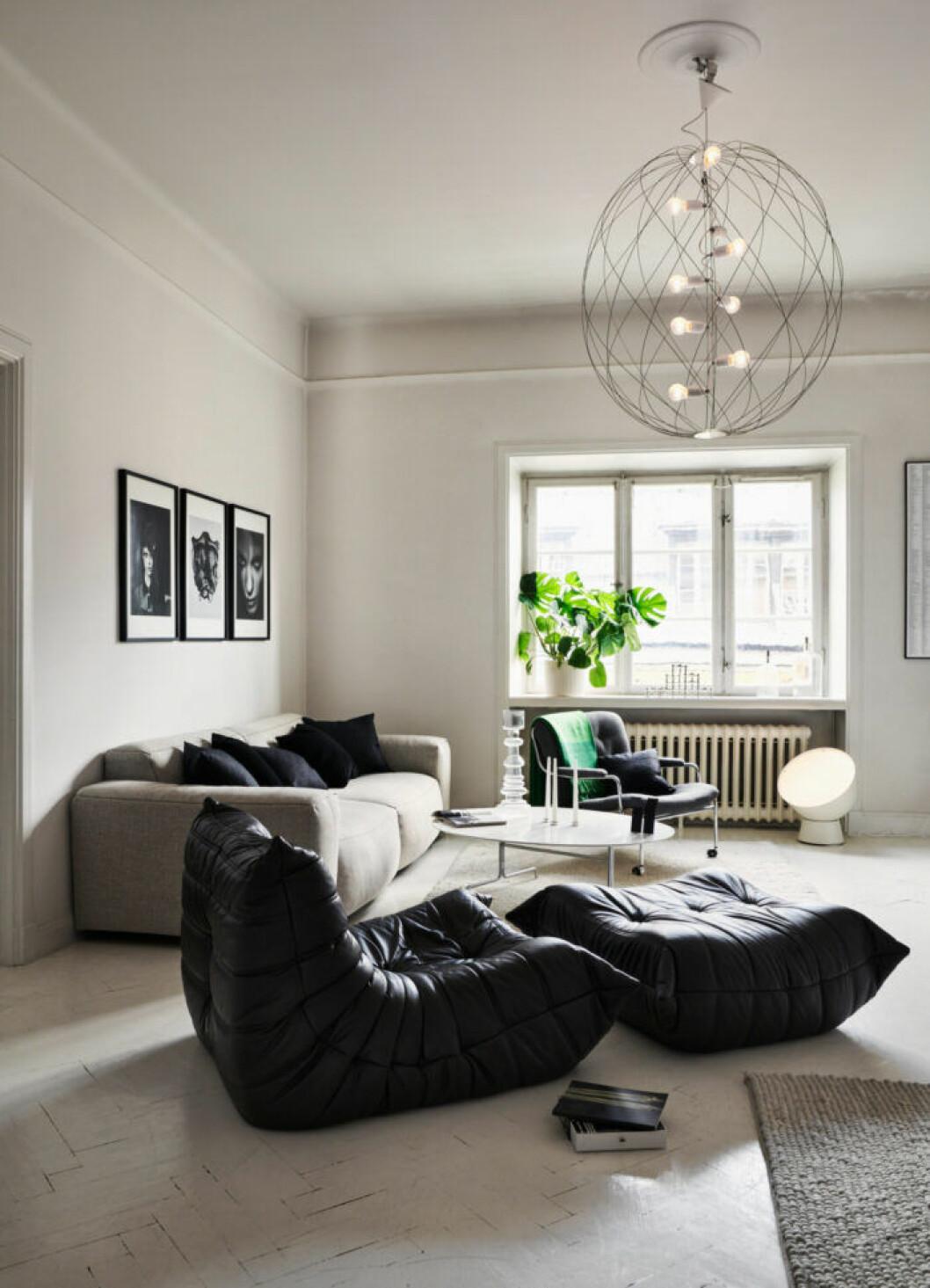 Svart fåtölj och fotpall i vardagsrummet hos modedesignern Lee Cotter i lägenheten i Stockholm