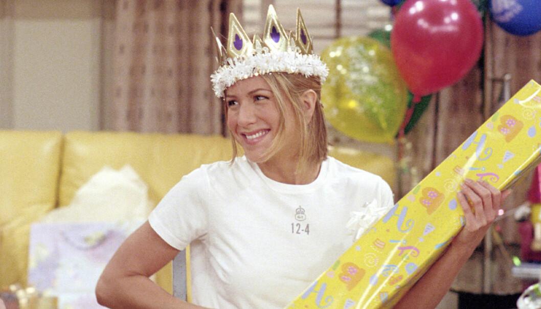Jennifer Aniston har en krona på huvudet och håller i ett gult paket