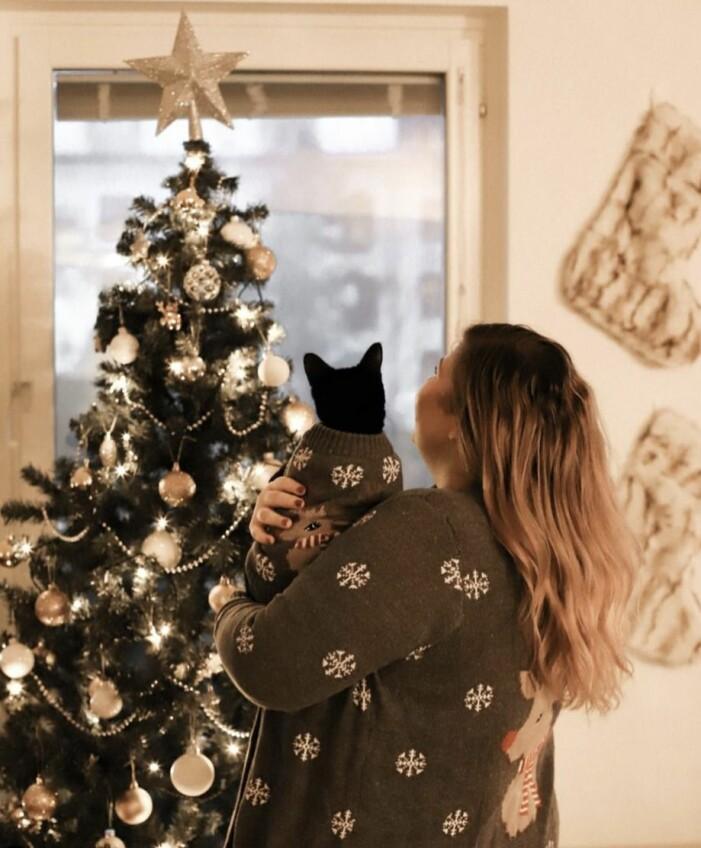 Linda-Marie Nilsson håller i en katt och tittar på sin julgran