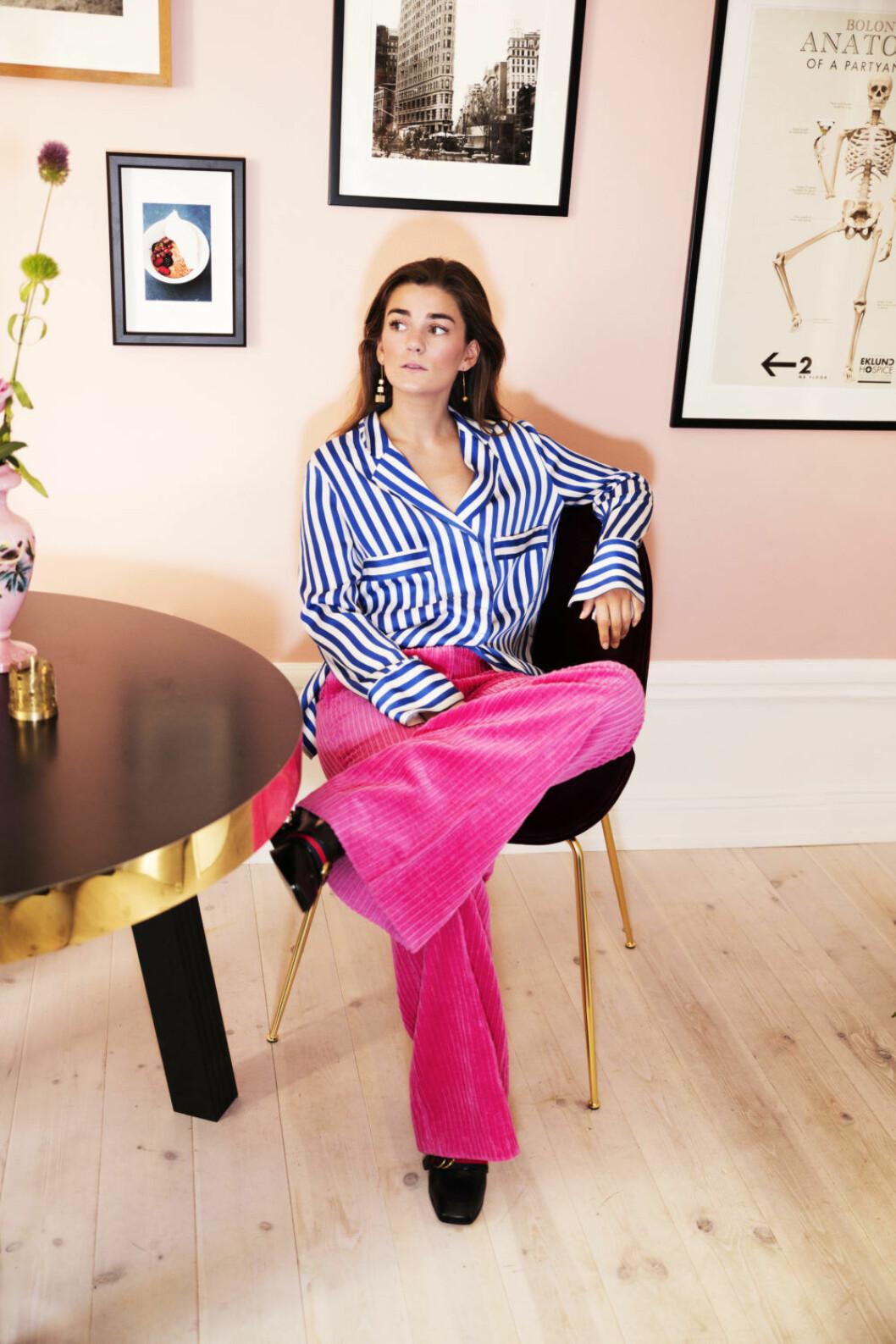 Linn Eklund i rosa byxor och blå och vit blus.