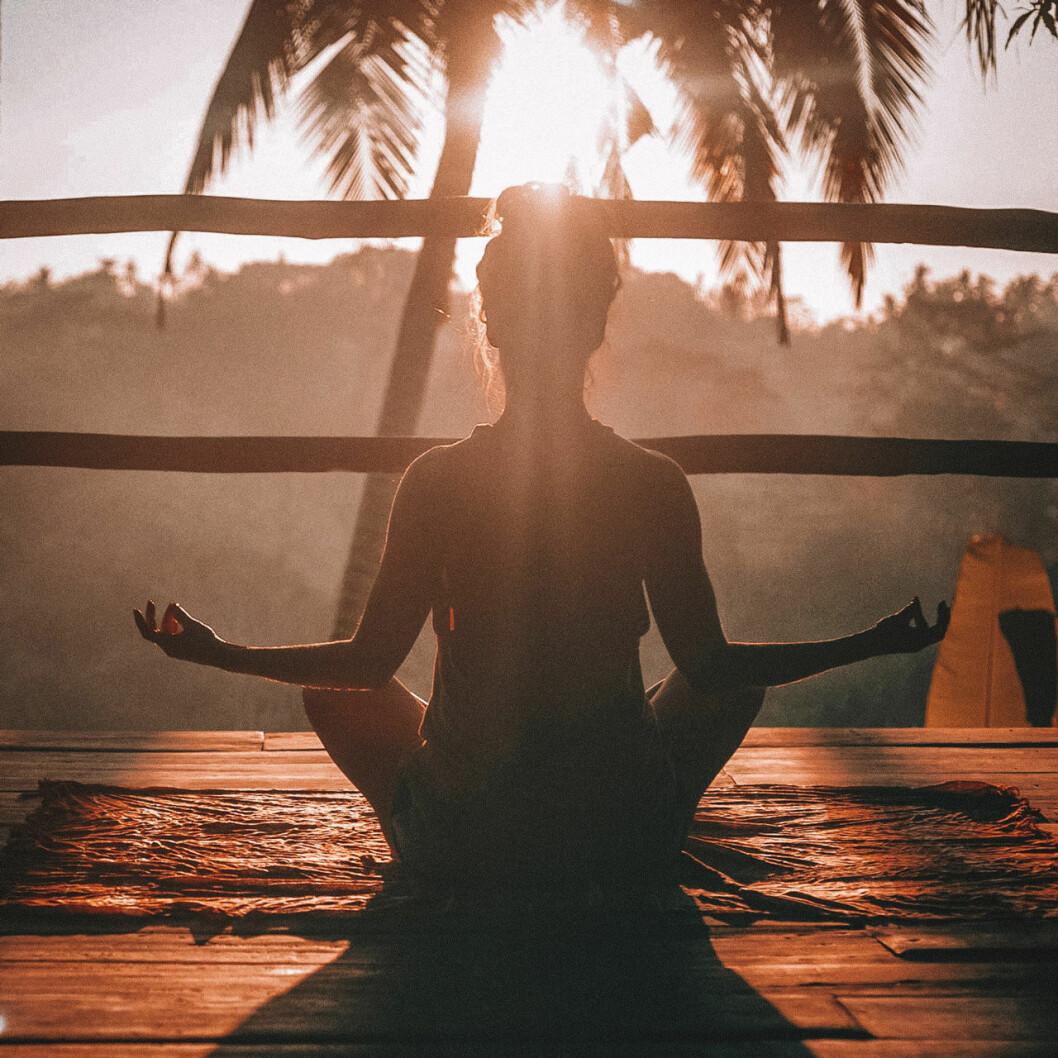kvinna yogar i solnedgång