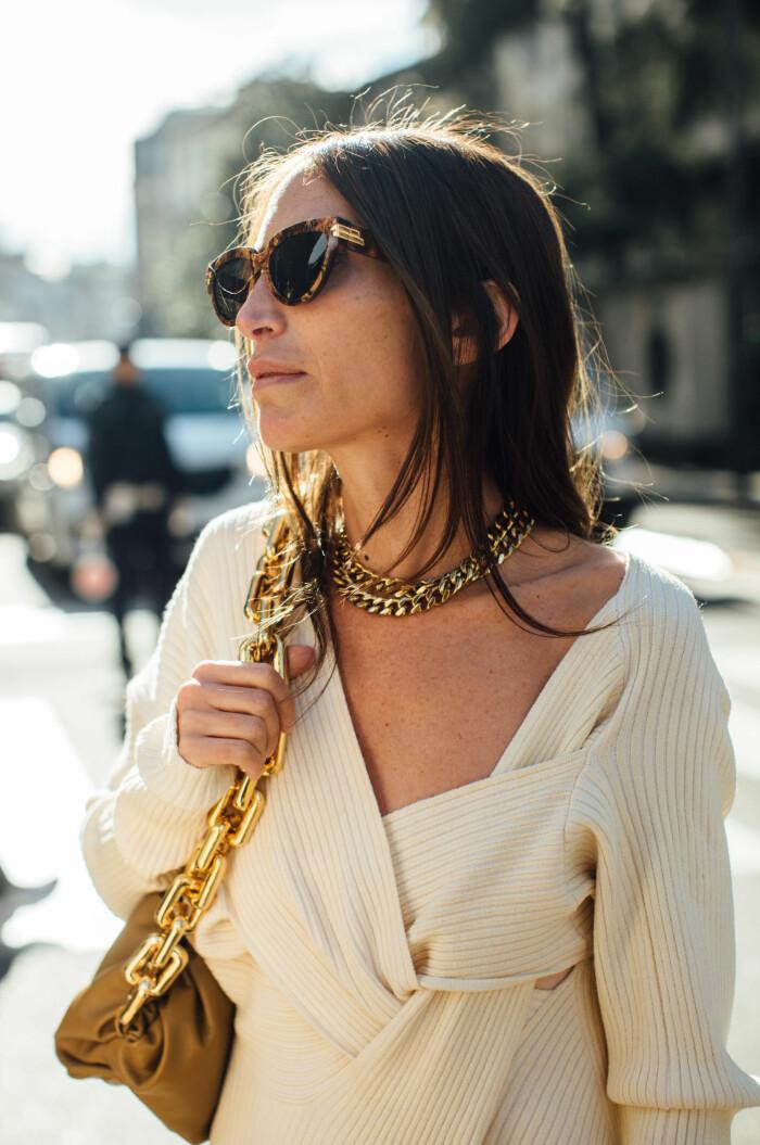 ljus ribbstickad tröja med smycken.