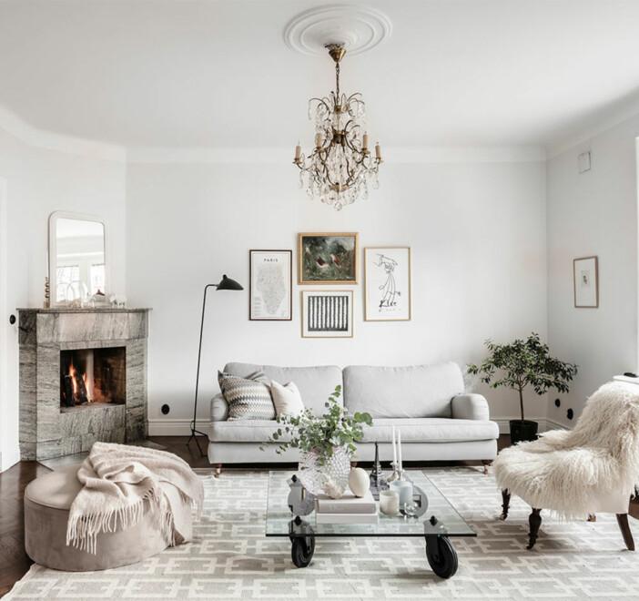 ljust vardagsrum med soffbord i glas och sittpuff i beige
