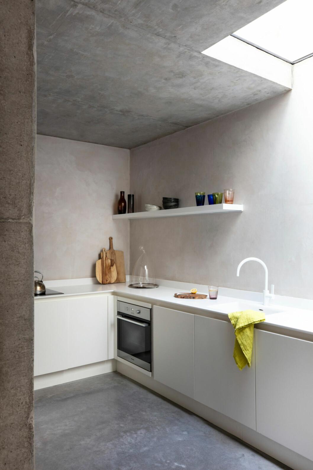 Köket går i sparsmakad stil i vita och gråa toner