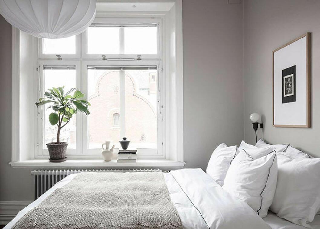 Lyxigt sovrum i hotellstil med vita lakan och tavla på väggen