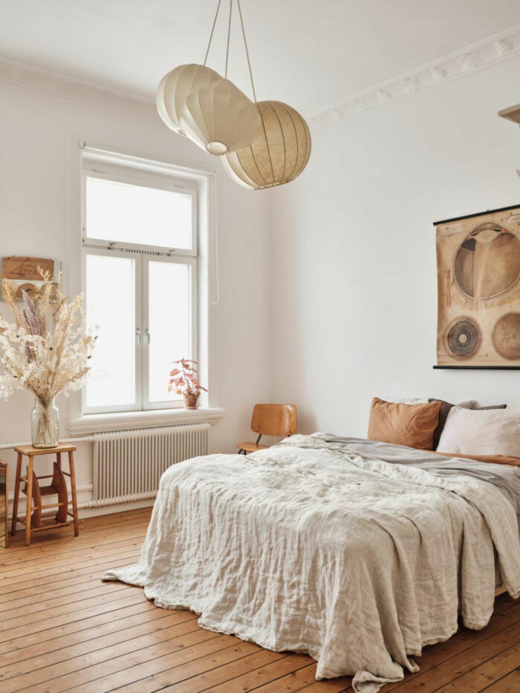 Sekelskifteslägenhet i Malmö, ljust sovrum med sfärisk belysning