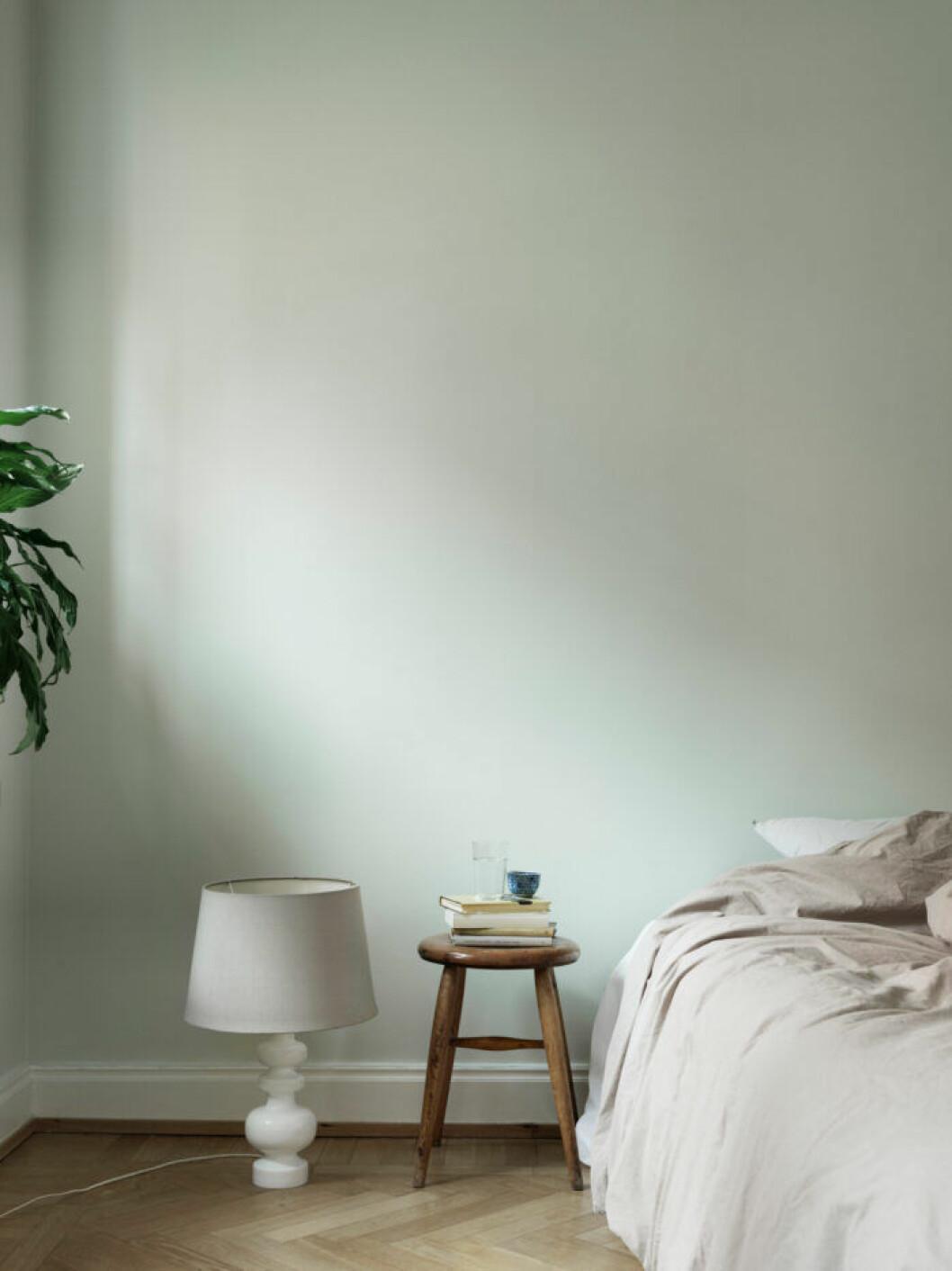 Ljusgrön vägg i sovrummet i lägenheten i Malmö