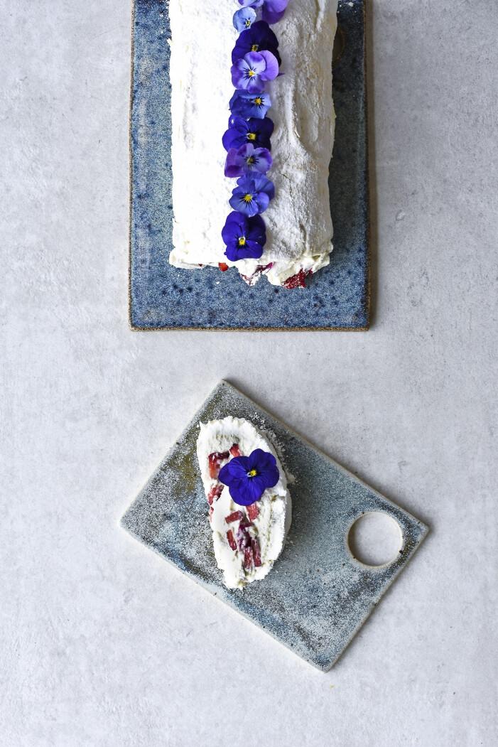 Baka en marängrulle med jordgubbar, rosenblad och violer