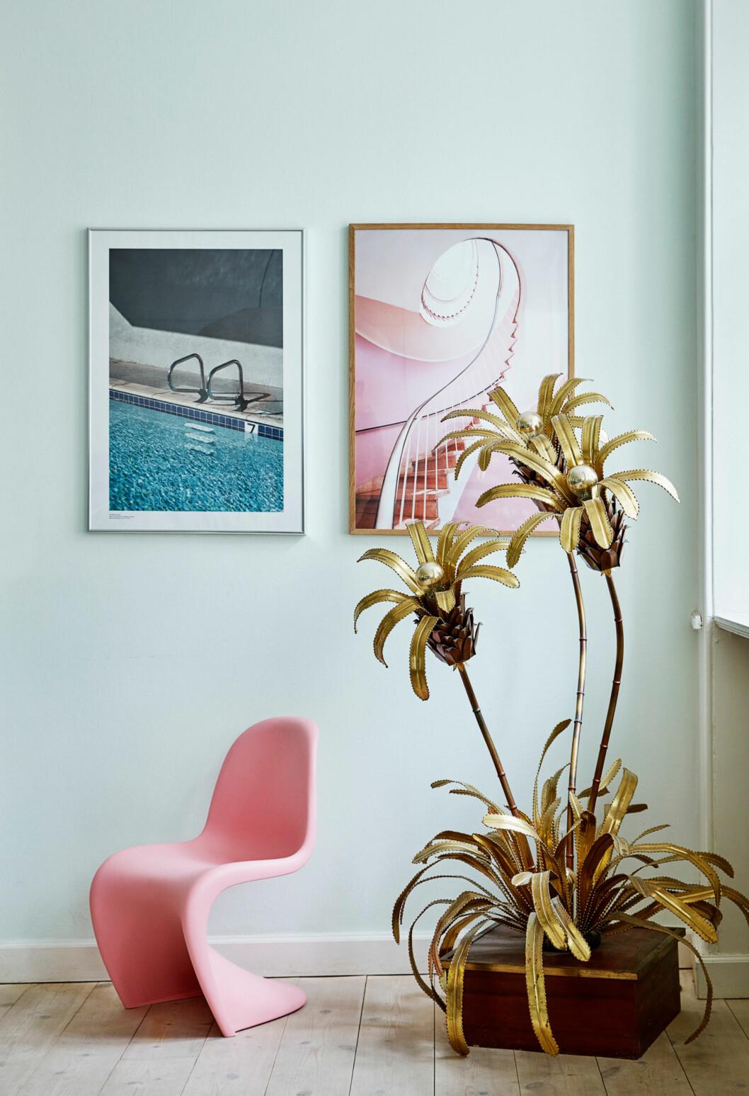 Rosa stol, palmdekoration och två tavlor i ett fint stilleben