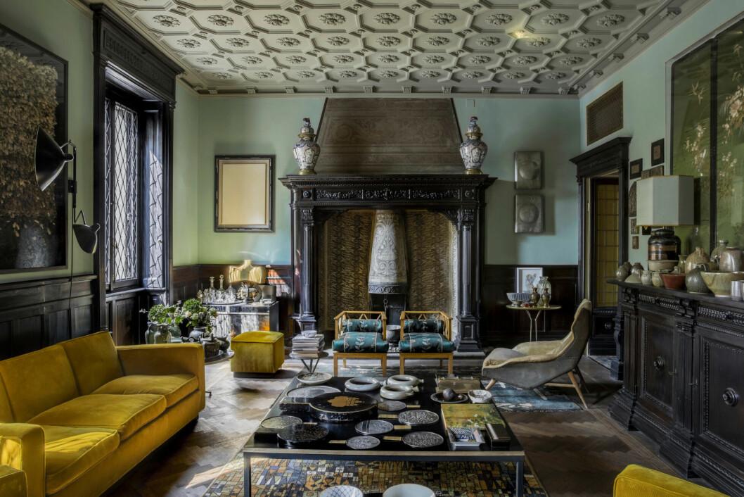 Ombonat vardagsrum i mörka trätoner, gult och gröna tapeter