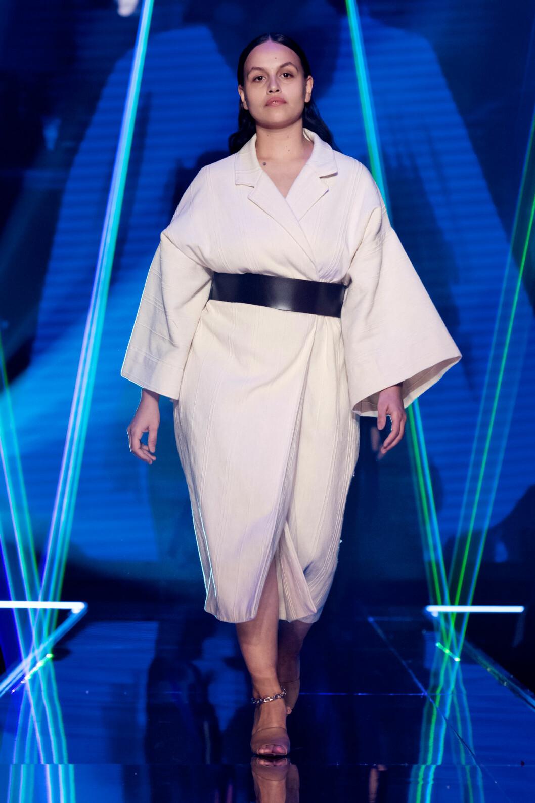 Vit kimonoklänning med svart markerad bälte i midjan från visningen av årets nykomling Amanda Borgfors Mészáros.