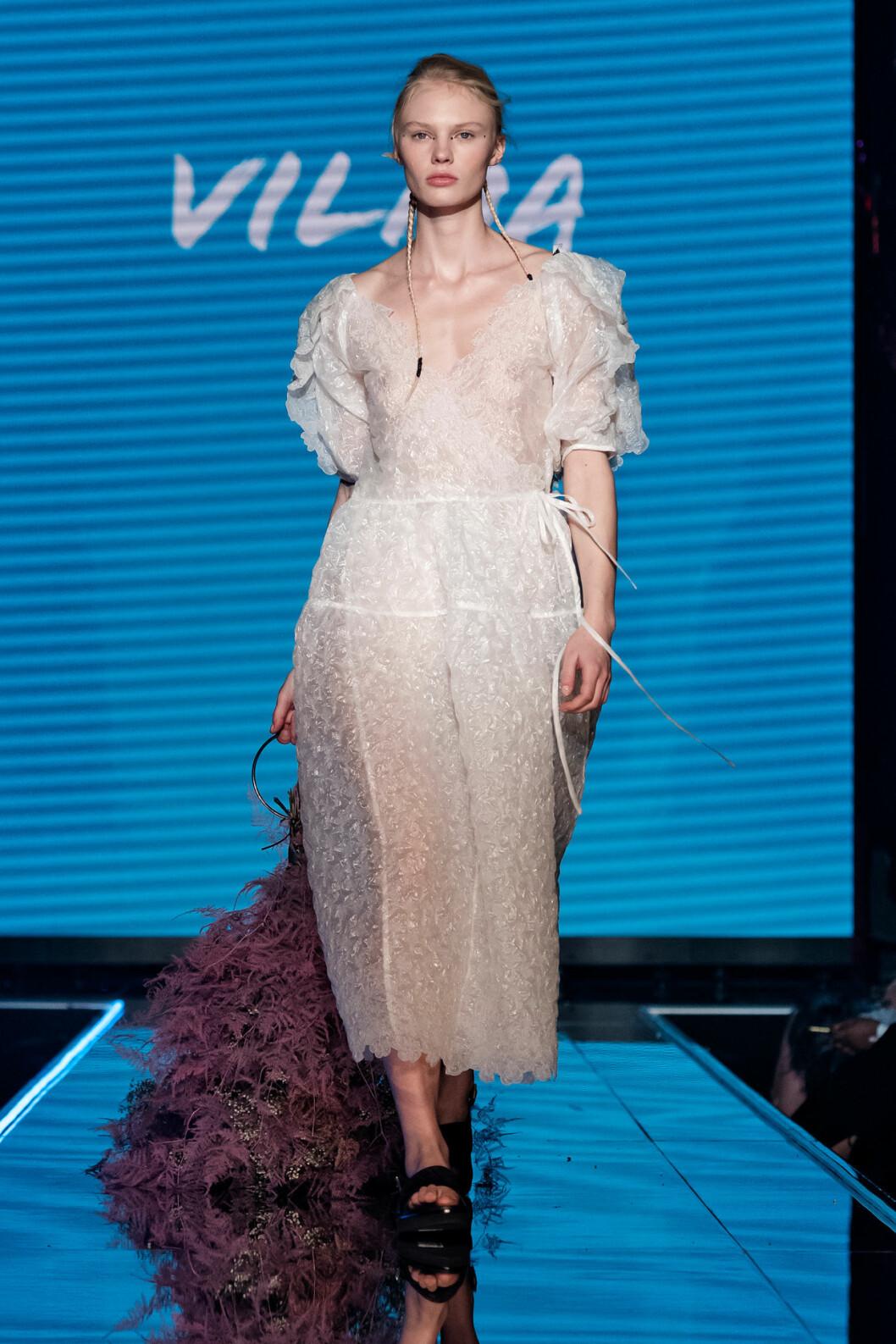Modell i vacker klänning och torkad blomsterkreation i rosa.