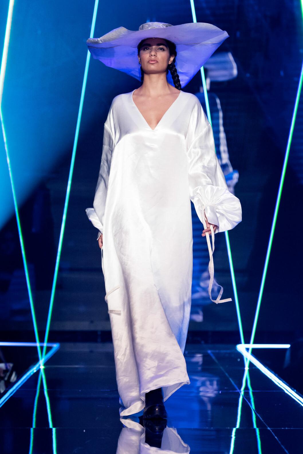 Vit klänning med stor huvudbonad från visningen av årets nykomling Amanda Borgfors Mészáros.
