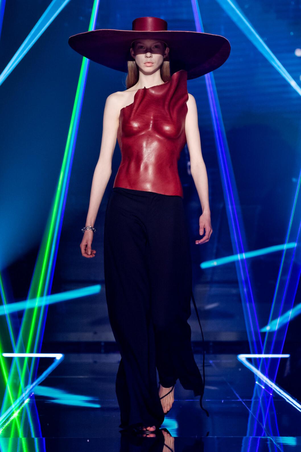 Skulptural överdel i rostig röd med matchande stor hatt från visningen av årets nykomling Amanda Borgfors Mészáros.