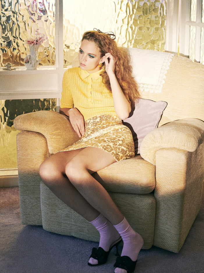 Modellen bär topp och kjol från Dolce & Gabbana, skor från Miu Miu, hårspänne från J&M Davidson, örhängen, vintage från Chanel/Susan Caplan och strumpor från Pantherella.
