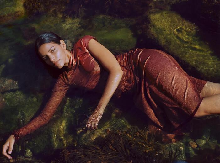 Modellen har på sig en röd topp och röd kjol från Acne Studios