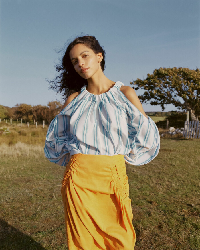 Modellen bär en randig blus och en gul kjol från Rejina Pyo