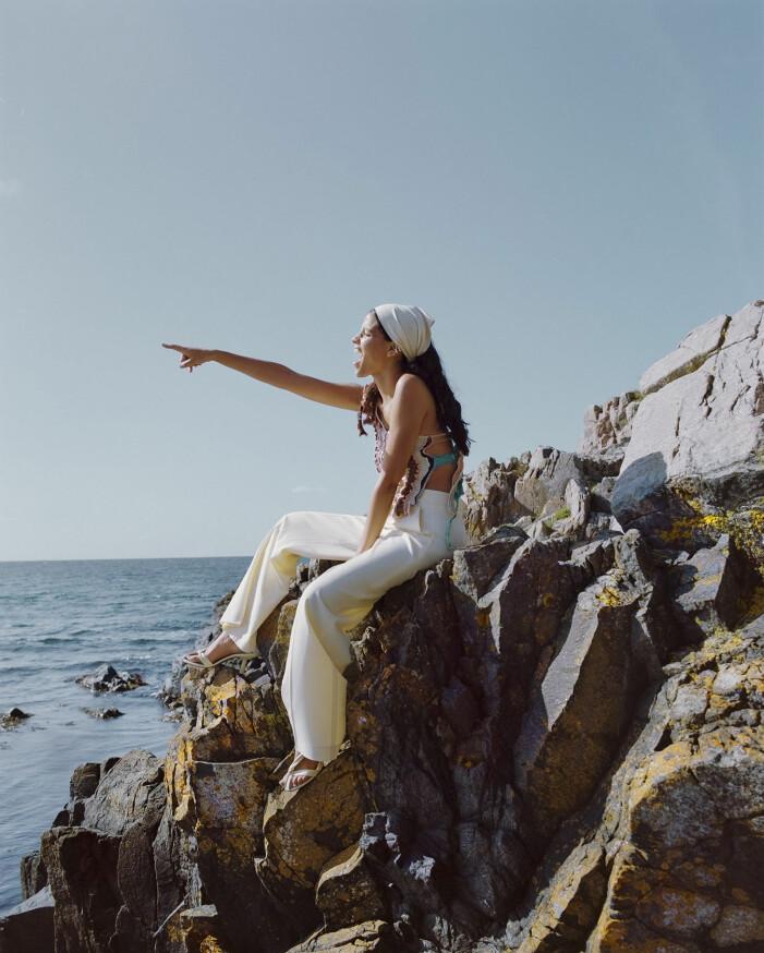 Modellen har på sig en mönstrad topp från Rua Carlota och vita byxor från Cos