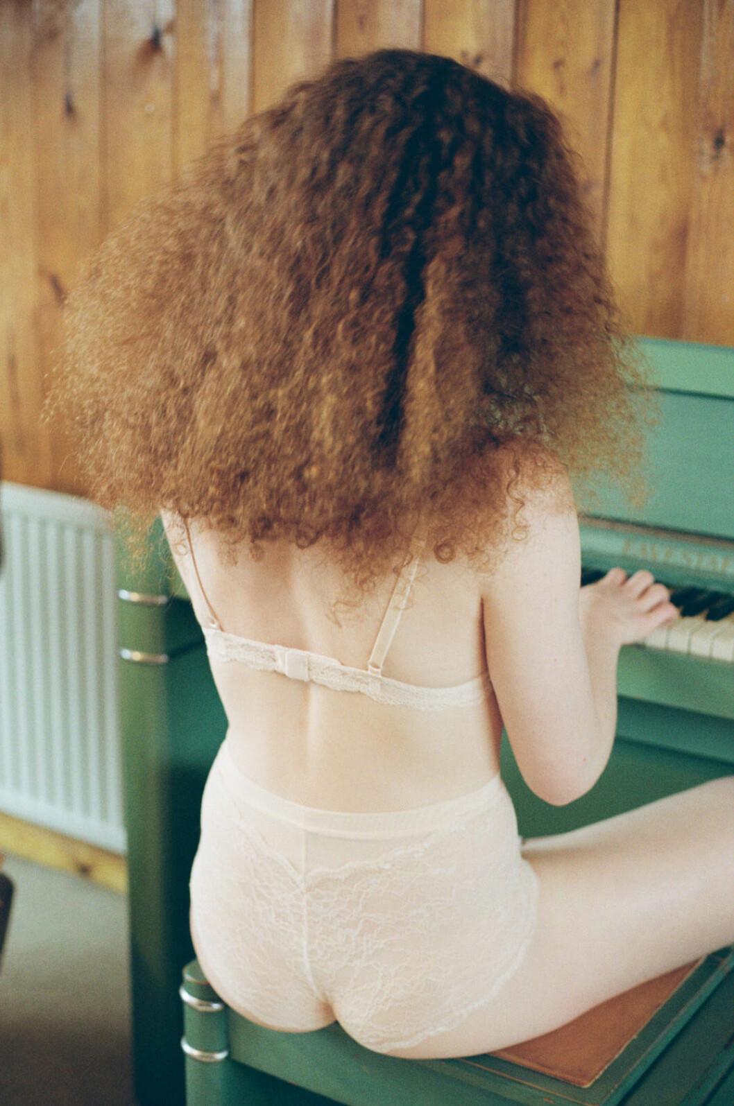 Krullhårig kvinna med väldigt ljus hy spelar piano i Monkis nya underkläder.