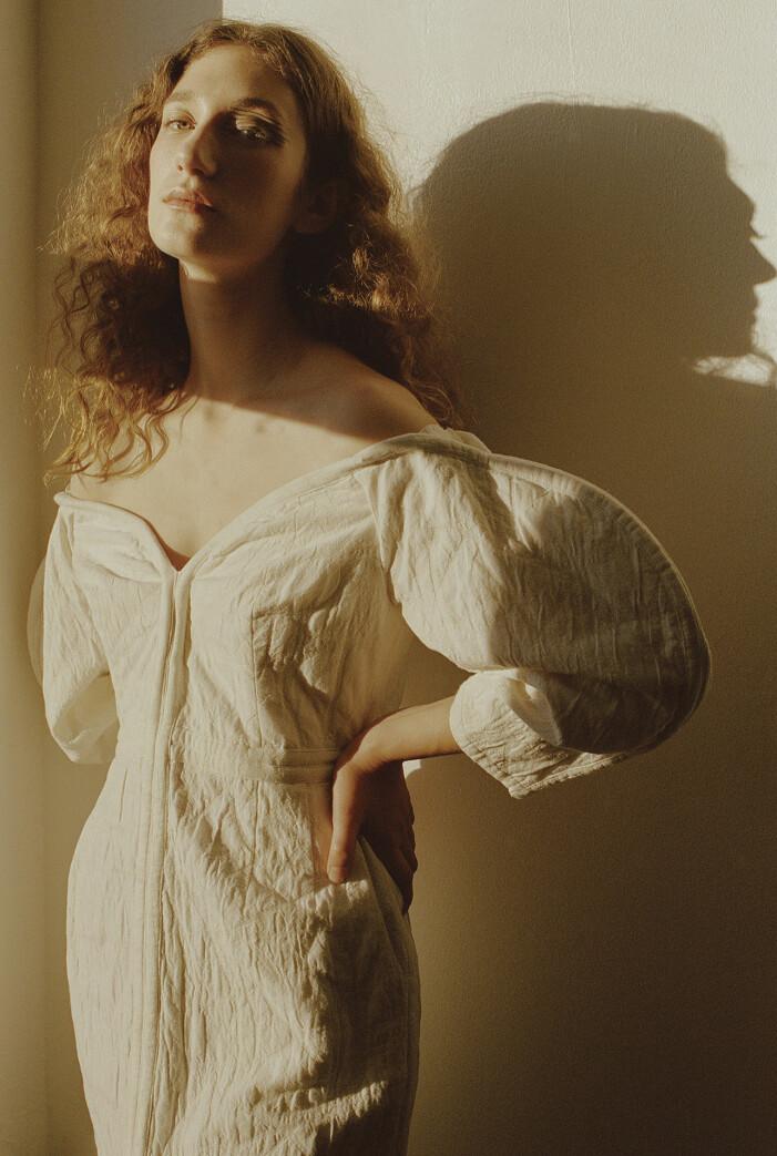Modellen bär en vit klänning från Mara Hoffman