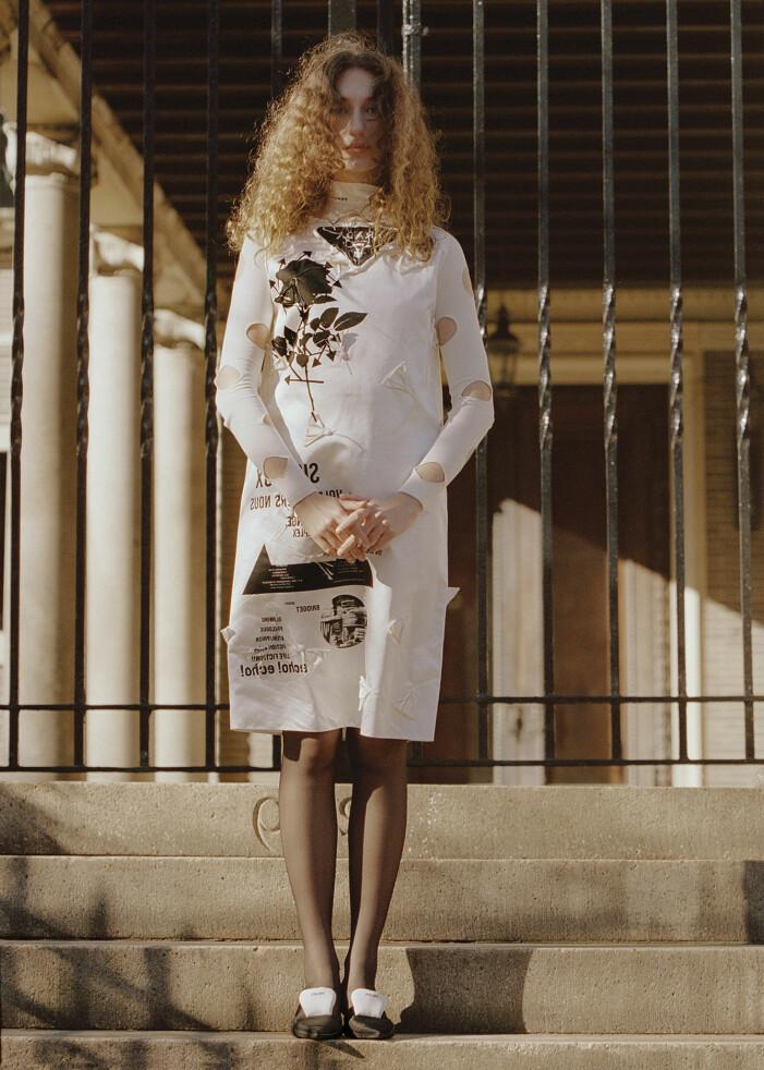 Modellen har på sig en vit klänning och svarta skor, båda från Prada