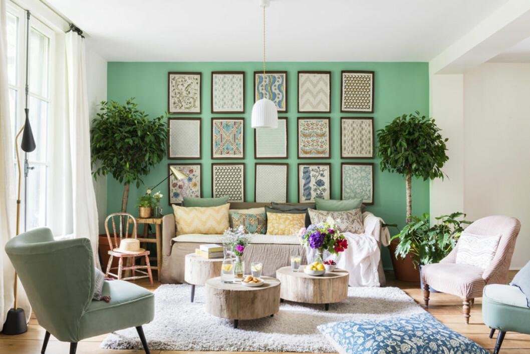 vardagsrummet med gröna väggar och en enhetlig tavelvägg som sätter stilen