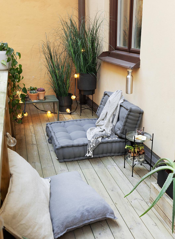 Mysig balkong med låga möbler och möbler på golvet