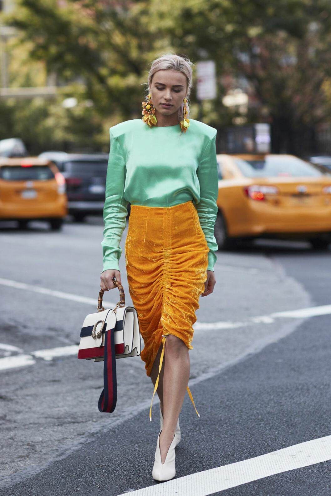 Grön sidentröja och orange kjol.