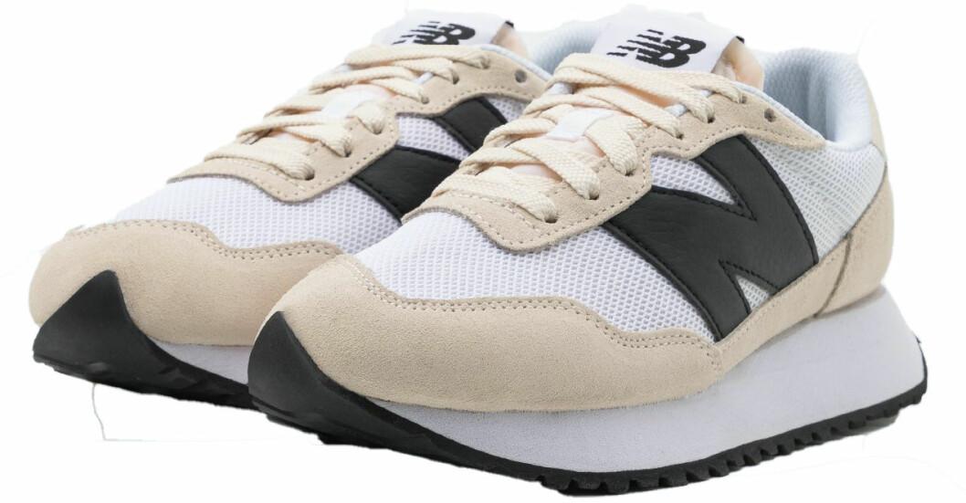 Sneakers i modell 237 i beige, svart och vitt från New Balance.