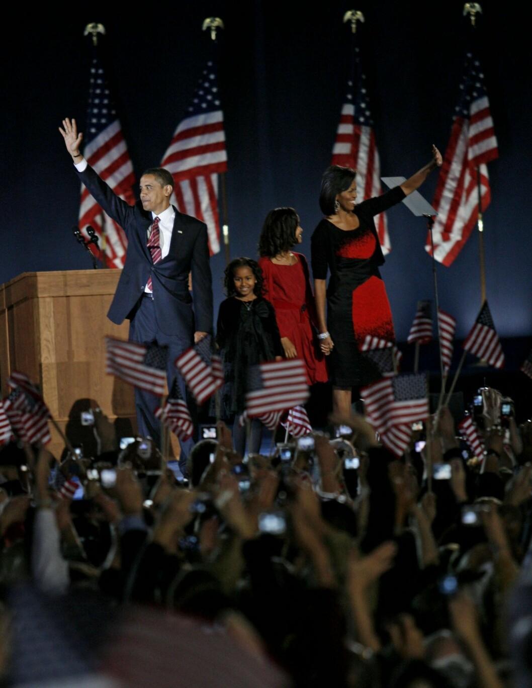 Familjen Obama står på en scen och vinkar till folkmassorna som viftar med amerikanska flaggor