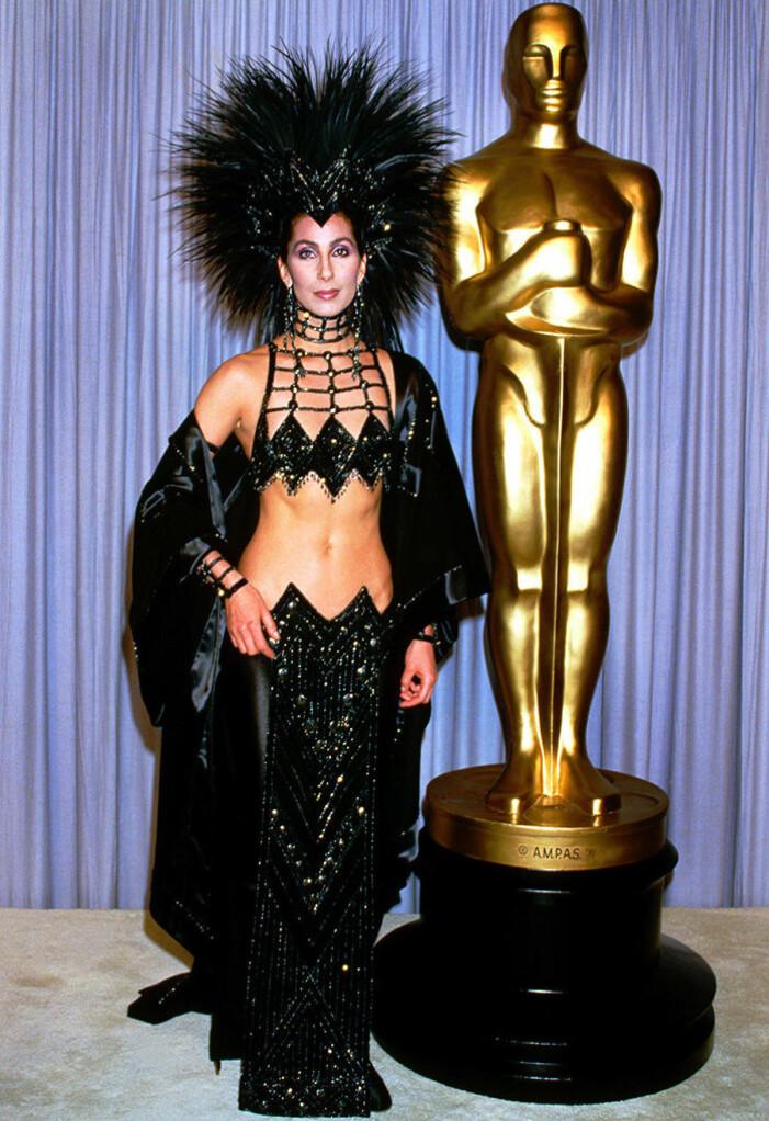 Cher i svart fjäderhatt och svart avslöjande zickzack-klänning
