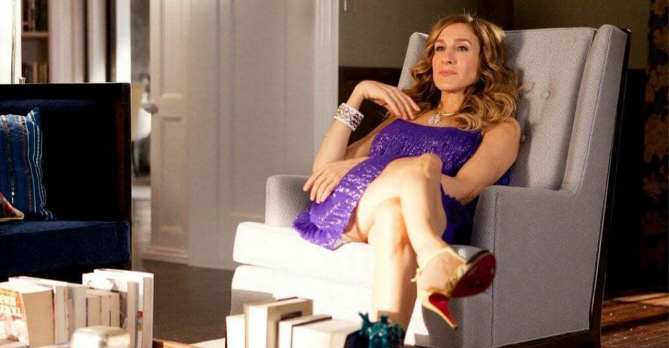 Carrie Bradshaw i Sex and the City sitter och tänker i en fåtölj