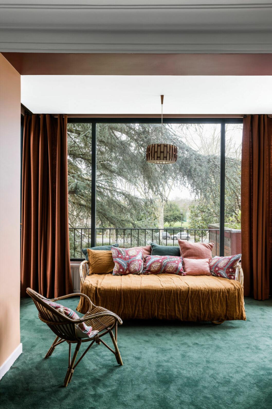 Mörkgrön heltäckningsmatta inramar ett ombonat rum med en stilfull dagbädd i rotting