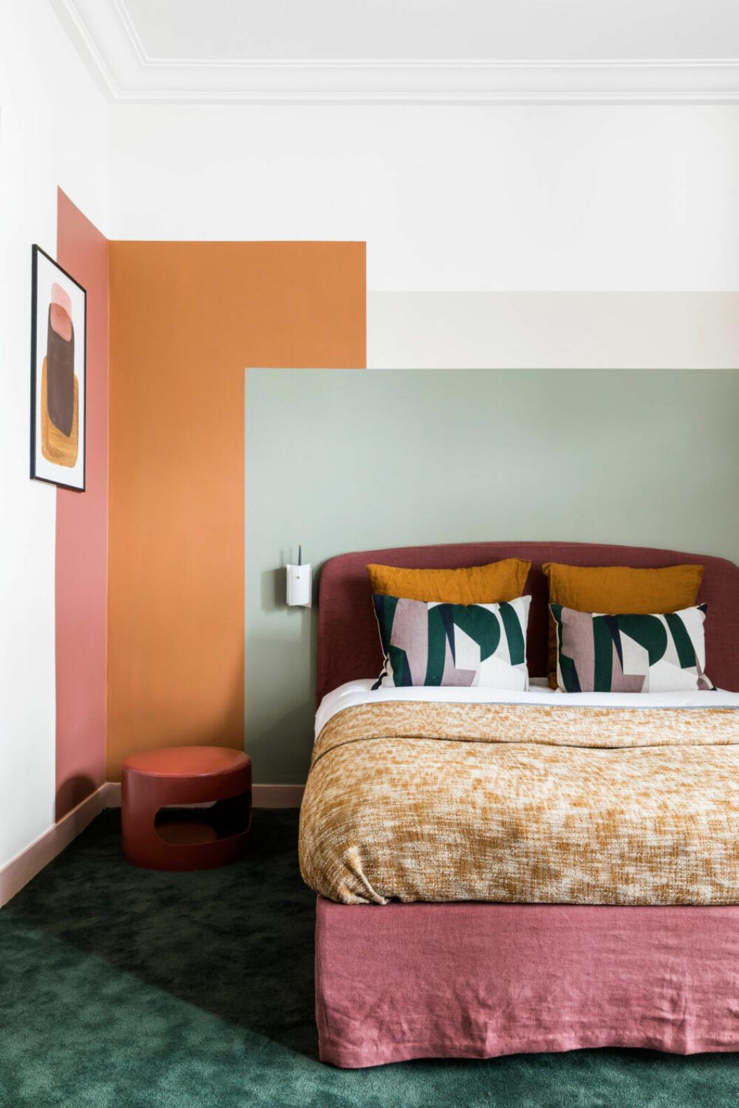 Färgglatt sovrum med orange-grön vägg och färgglada textilier på sängen