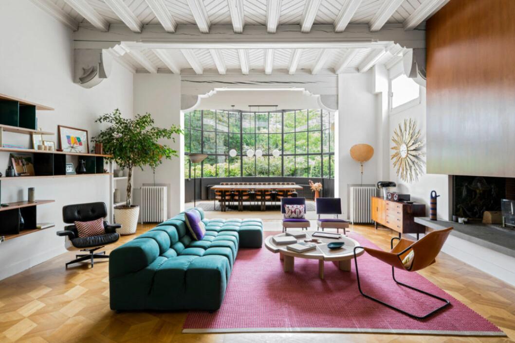 Vardagsrummet med turkos soffa, ljusrosa matta och mängder av färgglada små och stora inredningsdetaljer