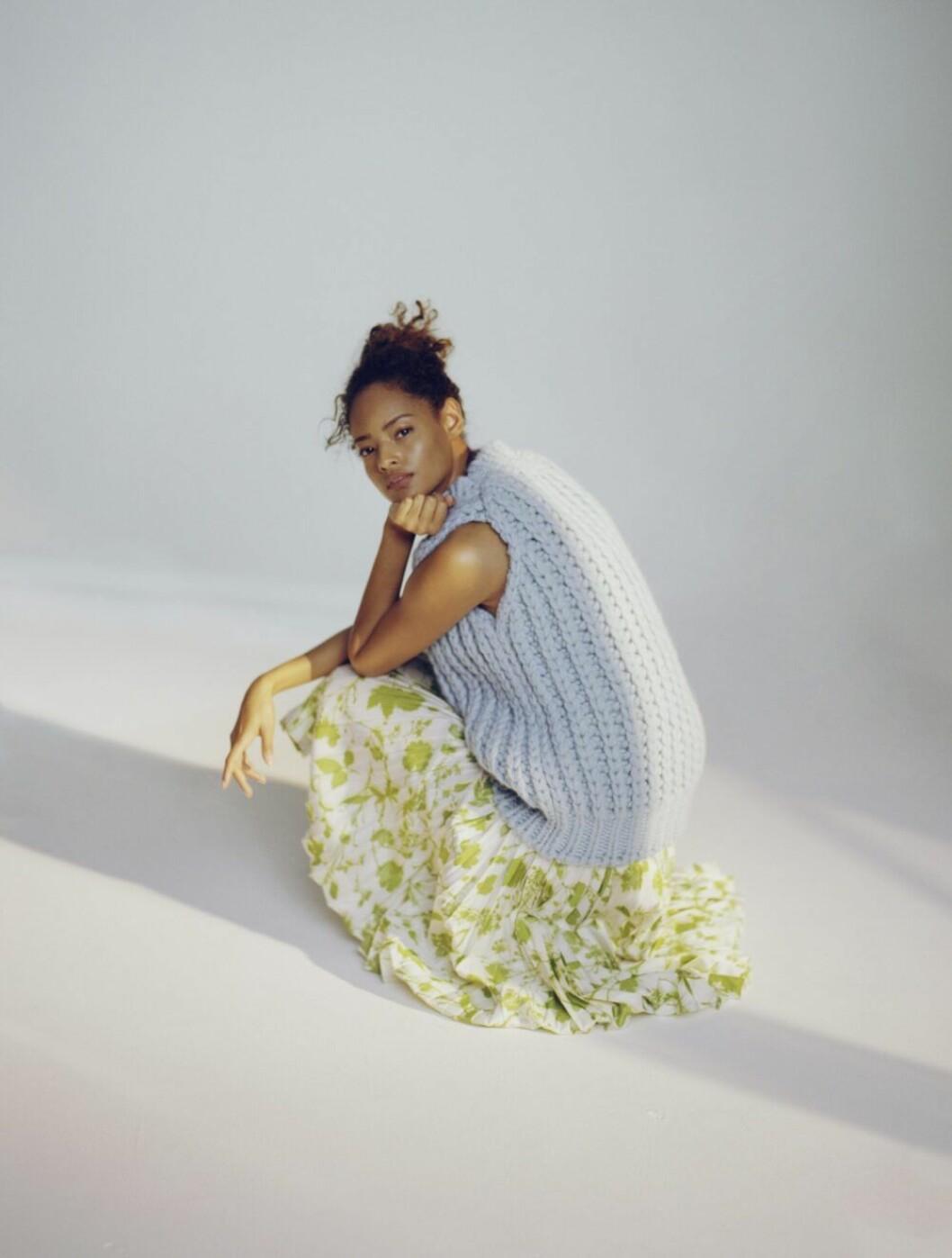 Stickad himmelsblå tröja och blommig kjol