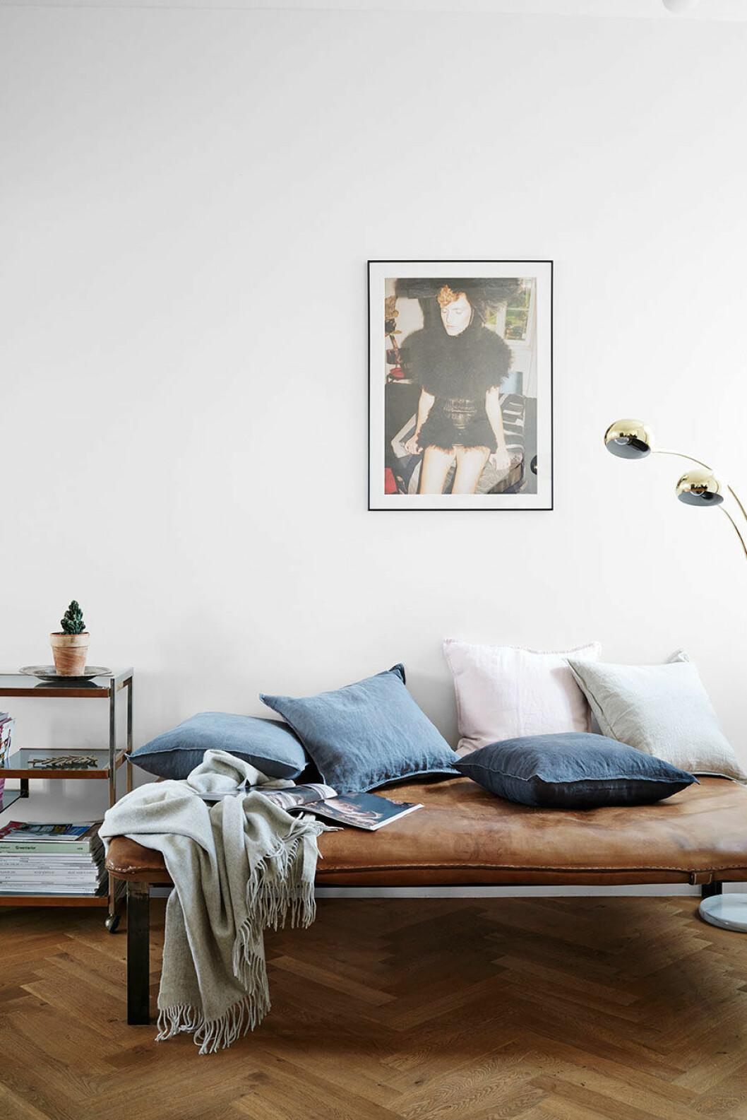 På dagbädden i väl patinerat läder ligger linnekuddar från H&M Home.
