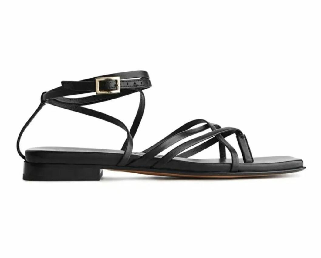 Dessa platta sandaler i svart med tunna remband och justerbart spänne från arket.