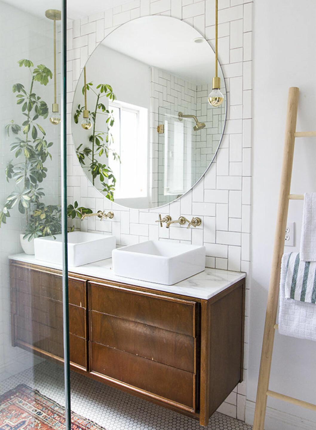 Badrum med träförvaring, rund stor spegel och kakel i vitt