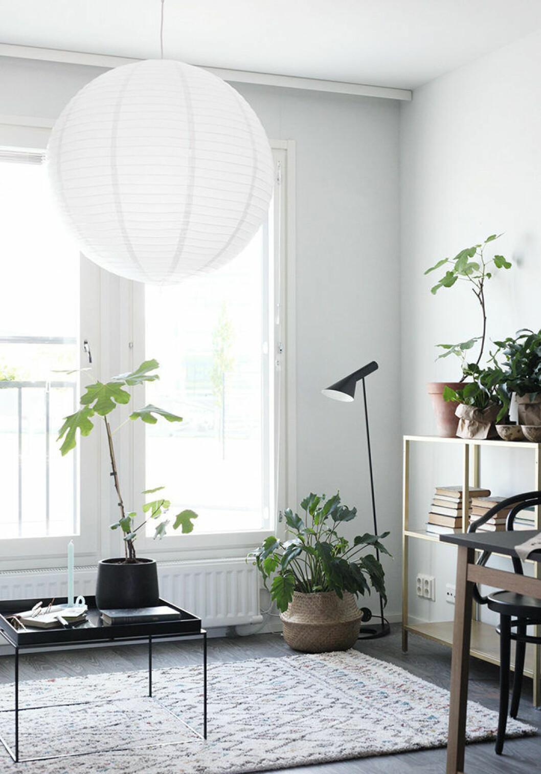 Stor lampa i rispapper i ett rum med balkong och växter