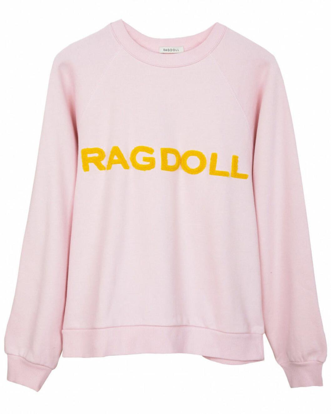 rosa mjukiströja med gul text från ragdoll.
