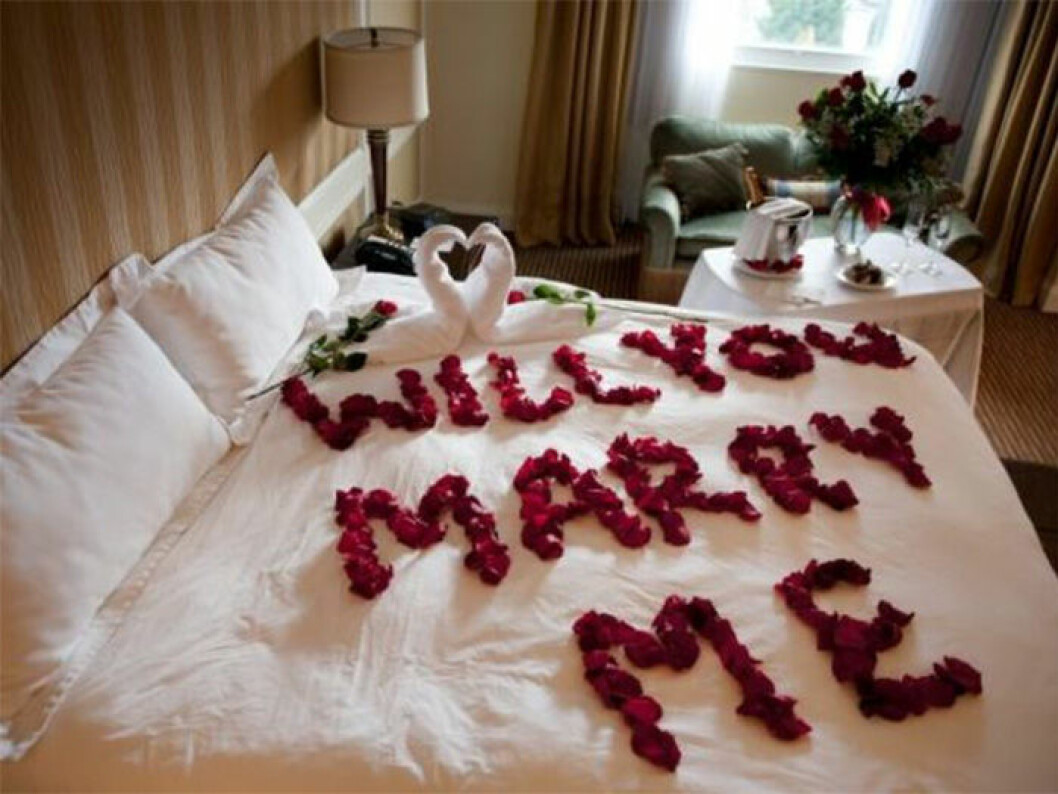"""Säng dekorerad med rosblad i texten """"Will you marry me?"""""""