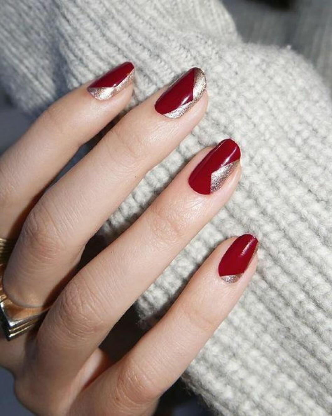 En bild på en nagellacksmanikyr i de juliga färgerna rött och guld.