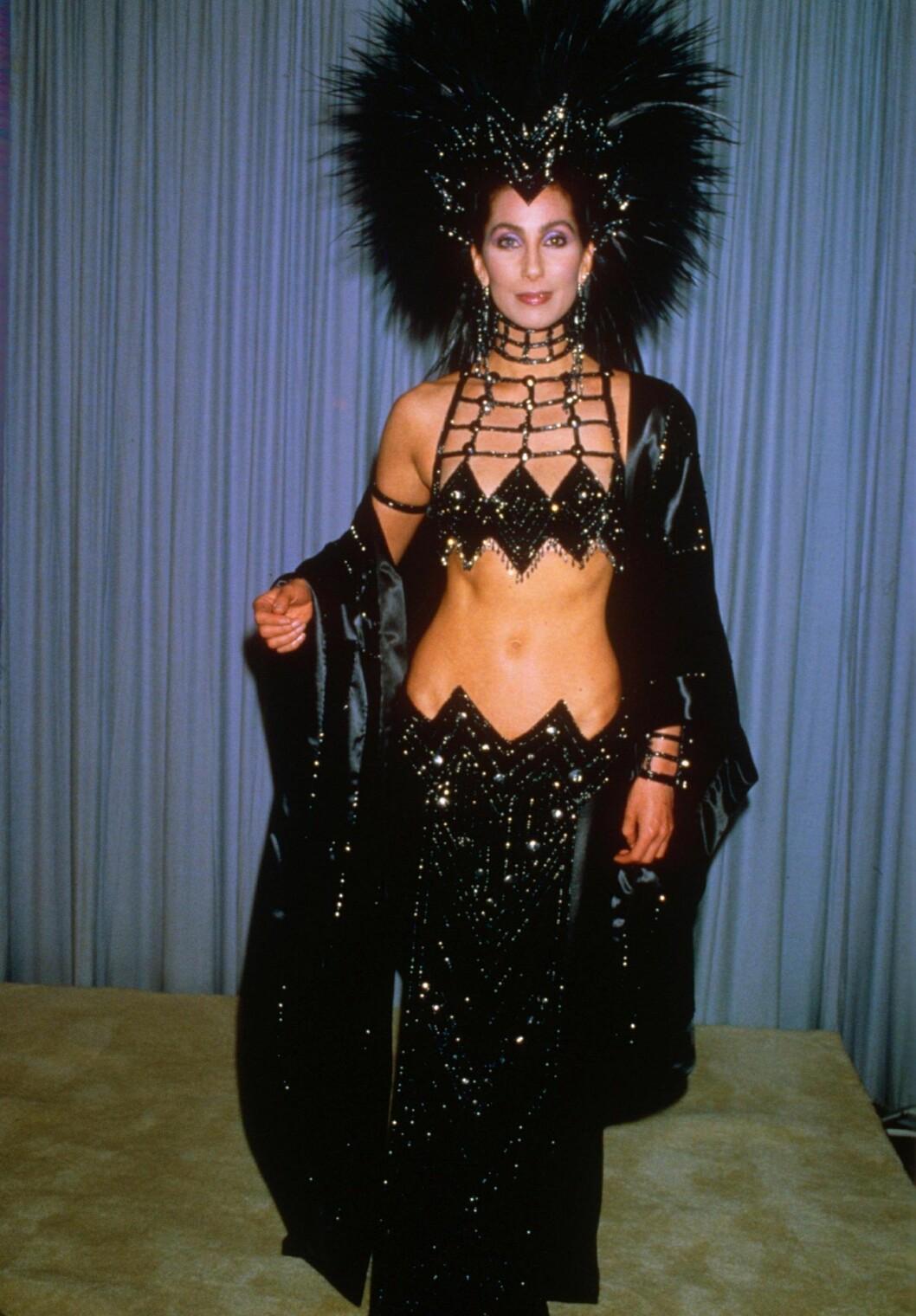 Cher i en svart glittrig showgirl kreation med en stor fjäderdekoration i håret.