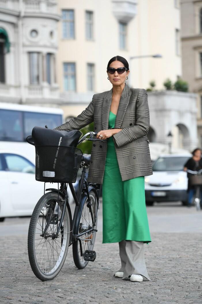 kvinna i en snygg våroutfit med klänning, byxor och kavaj