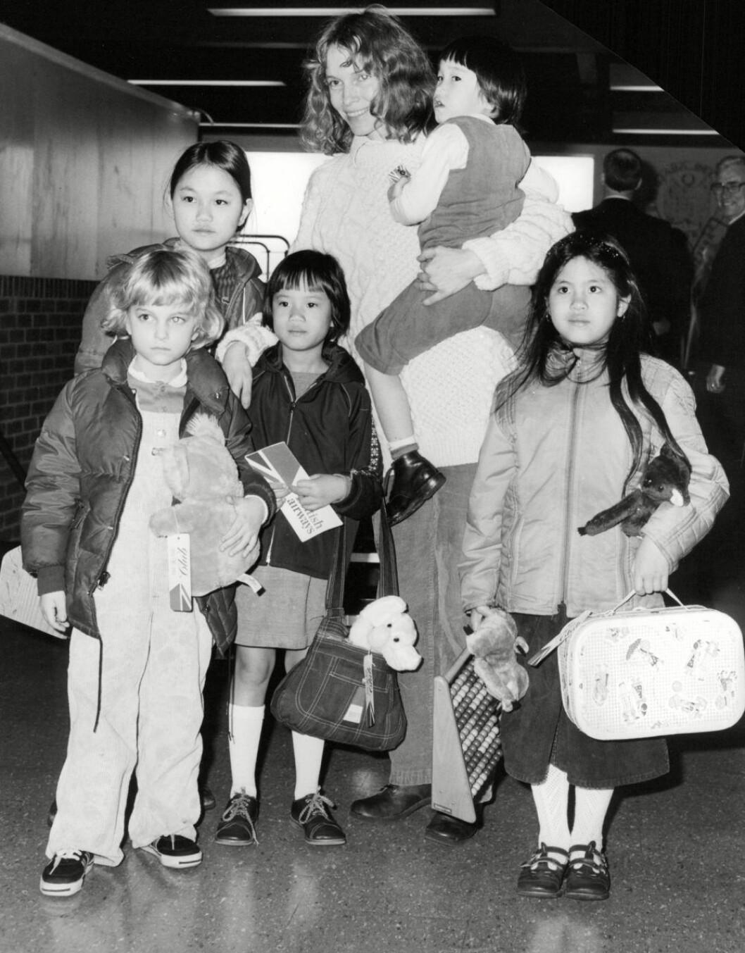 Mia Farrow med fem barn på en flygplats