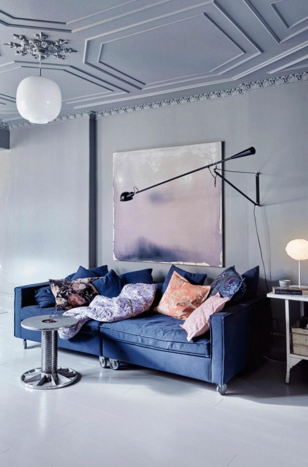 Blå soffa blir en bra kontrast i det gråmålade hemmet