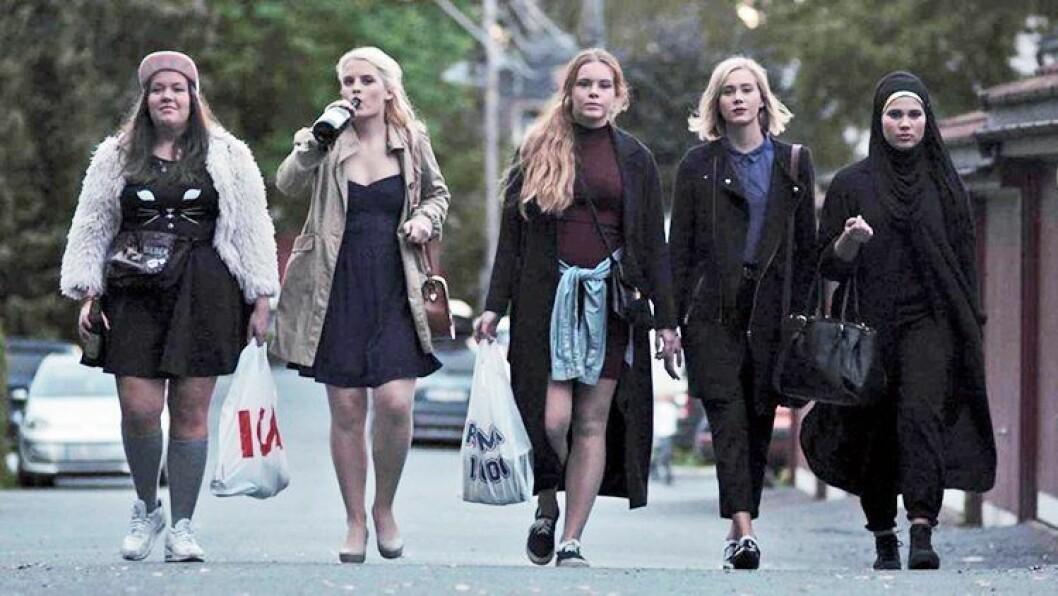 fem tjejer går i rad på en väg