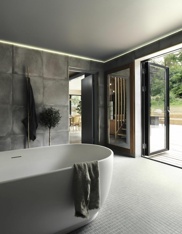 Stilrent badrum med grått kakel och makalös uteplats